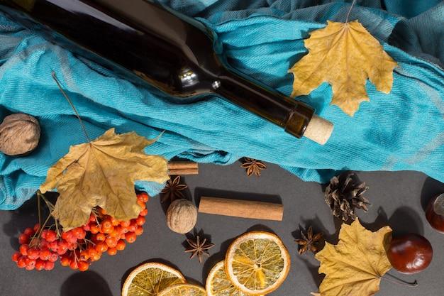 Een fles glühwein met kruiden, een sjaal, droge bladeren en sinaasappels op een stenen tafel. herfststemming, een methode om warm te blijven in de kou.