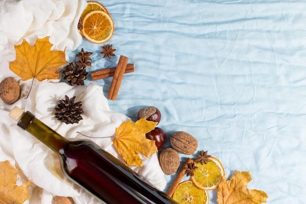 Een fles glühwein met kruiden, sjaal, droge bladeren en sinaasappelen op een tafel. herfststemming, een methode om warm te blijven in de kou, copyspace.