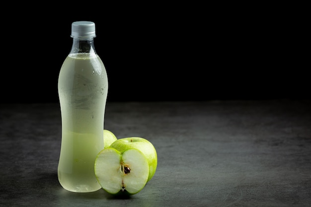 Een fles groene appel gezond sap naast verse groene appels