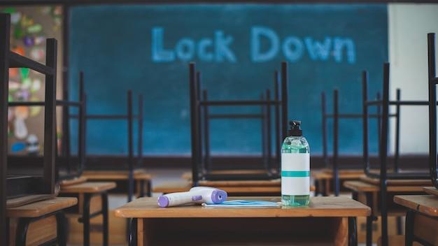 Een fles handdesinfecterend middel, digitale thermometer en gezichtsmasker staan op een tafel in de klas op een school. de school is gesloten vanwege de covid-19-uitbraak en een bericht