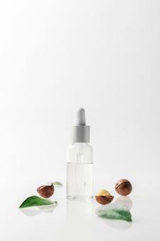 Een fles macadamia-notenolie op een grijze muur.