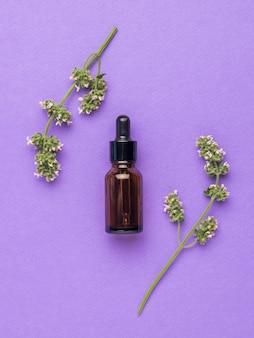 Een fles medicijnen en geneeskrachtige kruiden op een paarse achtergrond. plat leggen.