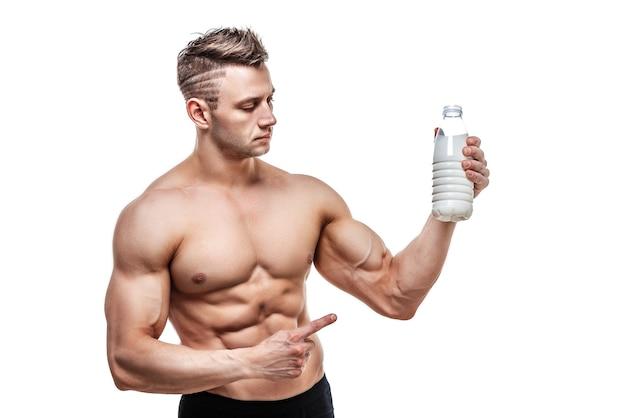 Een fles melk in zijn hand, een man met een sportief lichaam die zich voordeed op een witte muur.