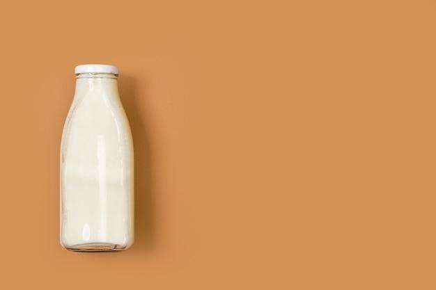 Een fles melk op een bruine achtergrond in een bovenaanzicht