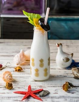 Een fles melkachtige shake met zeeschelpen.
