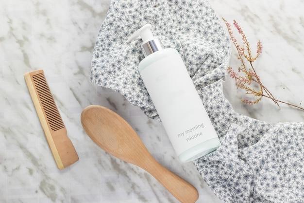 Een fles met douchegel, een borstel en een haarkam met een stuk stof met bloemen op een marmeren tafel