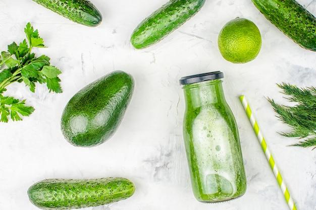 Een fles met een komkommersmoothie. versgeperst komkommersap met limoen en avocado. plat leggen, ingrediënten.