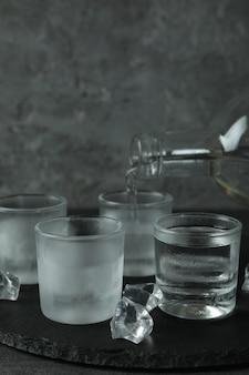 Een fles met schenkende drank en schoten van drank op zwarte dienblad