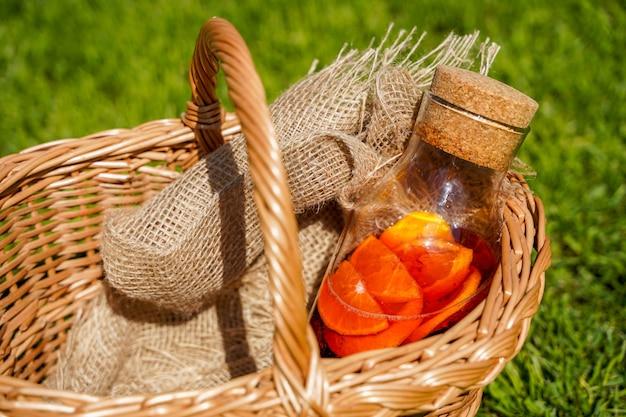 Een fles natuurlijke zelfgemaakte frisdrank met bessen en sinaasappels puur biologisch eten en drinken in een sinaasappelsap in rustieke stijl en een mand op het groene gras