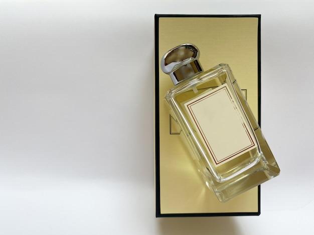 Een fles parfum uit een gele doos op een witte geïsoleerde achtergrond