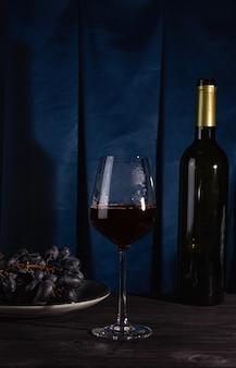 Een fles rode wijn, een glas en druiven op een donkere achtergrond.
