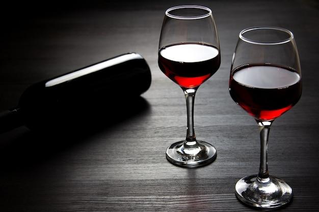 Een fles rode wijn en twee glazen rode wijn op donker