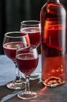 Een fles roze wijn met drie glazen op een stenen tafel.