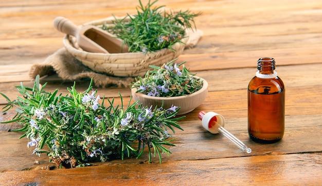 Een fles rozemarijn etherische olie op een houten tafel met bos rozemarijn