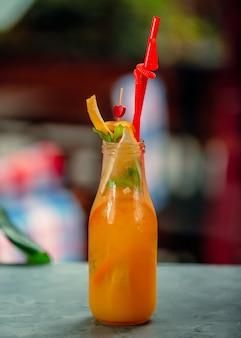 Een fles sinaasappelsap met stukjes sinaasappel en rood plastic rietje