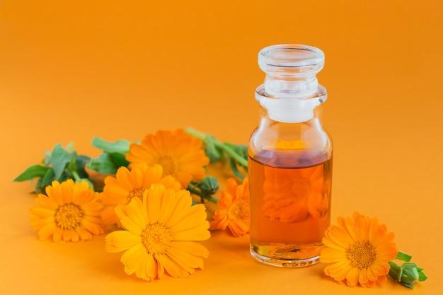 Een fles tinctuur van goudsbloem, met verse calendulabloemen op sinaasappel