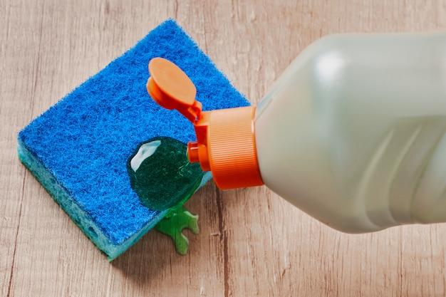 Een fles wasmiddel gel voor gerechten, sponzen op tabelachtergrond. bovenaanzicht