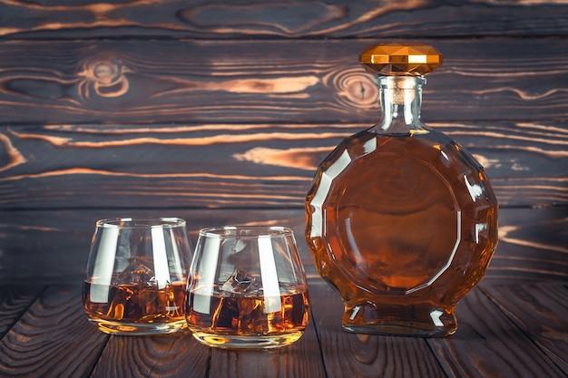 Een fles whisky en twee glazen op een donkerbruine houten tafel. transparante gele alcoholische drank met ijs. brandewijn, bourbon. sterke alcoholische drank. rum, whisky. stilleven in rustieke stijl.