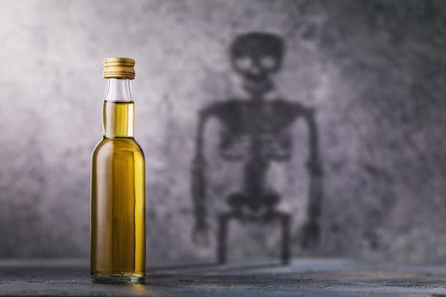 Een fles whisky met een schaduw in de vorm van een skeletconcept over de schade van alcohol en schadelijke gewoonten van de mens