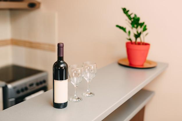 Een fles wijn en twee lege glazen op de bar in de keuken