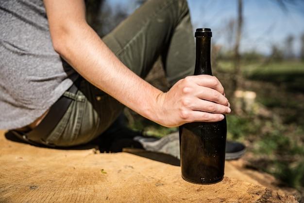 Een fles wijn in de hand van een man, alcohol drinkend in de natuur