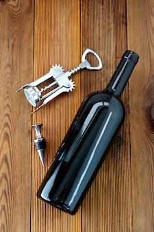Een fles wijn met corckscrew, houten rustiek. plat lag wijn drinken met copyspace.