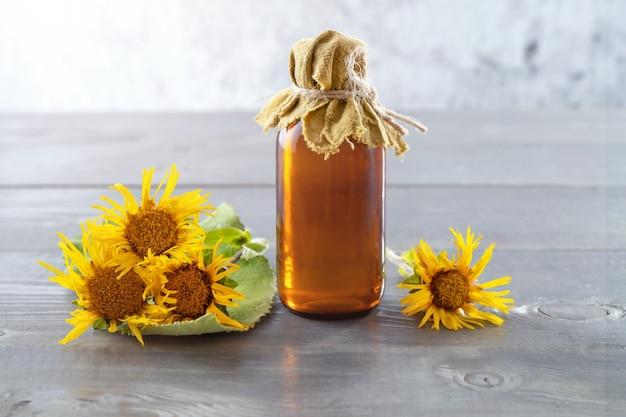 Een fles zelfgemaakte tinctuur van elecampane en bloemen