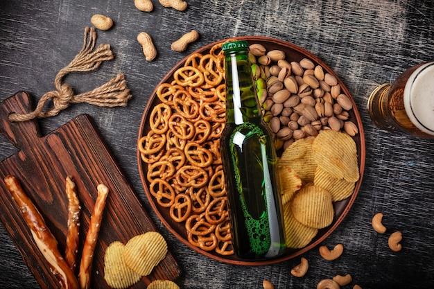 Een flesje bier op een bord met gezouten ookies pretzels, pistachenoten en chips op een zwart gekrast krijtbord