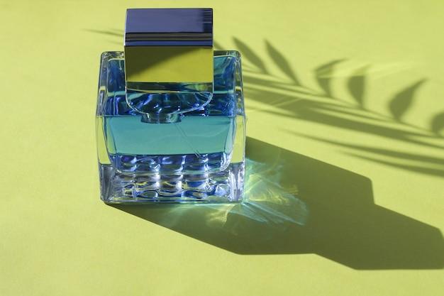 Een flesje blauw parfum op een gele achtergrond met lange schaduwen van de fles en een palmtak in de felle zon overdag.