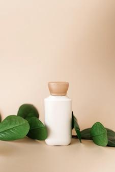 Een flesje crème voor de huidverzorging van het gezicht of lichaam met bladeren van zamiokulkas