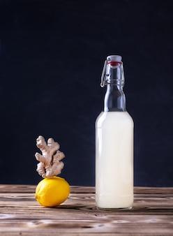 Een flesje huisgemaakte gemberbier citroen en gemberwortel