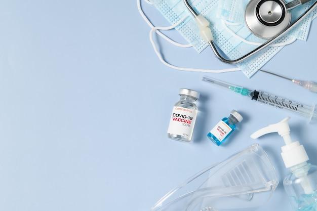 Een flesje met het covid 19-vaccin met spuit en stethoscoop op een chirurgisch masker op blauwe achtergrond, preventie van coronavirus of covid-19-uitbraakconcept