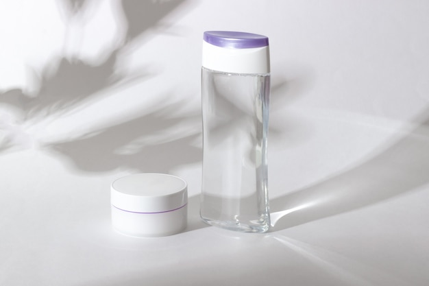 Een flesje micellair water en gezichtscrème met gegroefde bladeren op de achtergrond. makeup verwijderaar. biologische cosmetica concept.