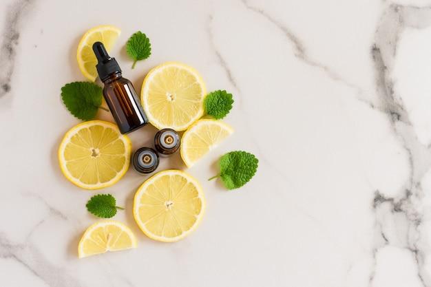 Een flesje serum en twee flesjes met een druppelaar essentiële citroenolie voor de huidverzorging van het gezicht en lichaam. bovenaanzicht. het concept van zorg en spa.