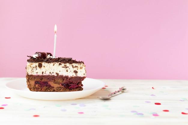 Een fluitje van een cent met een kaars, een taart voor een verjaardag, ruimte voor tekst