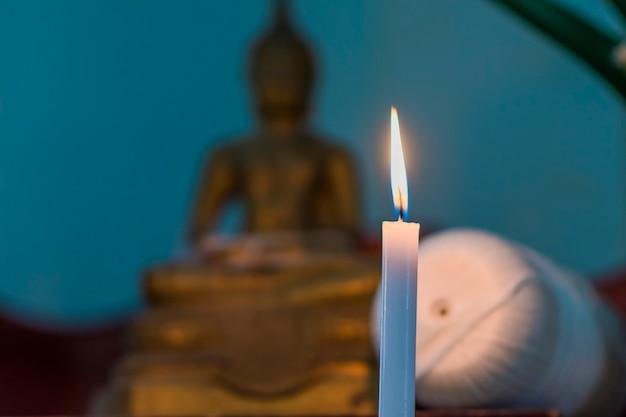Een focusbeeld van een kaars die op de voorgrond schijnt en de achtergrond van het boeddhabeeld vervaagt.