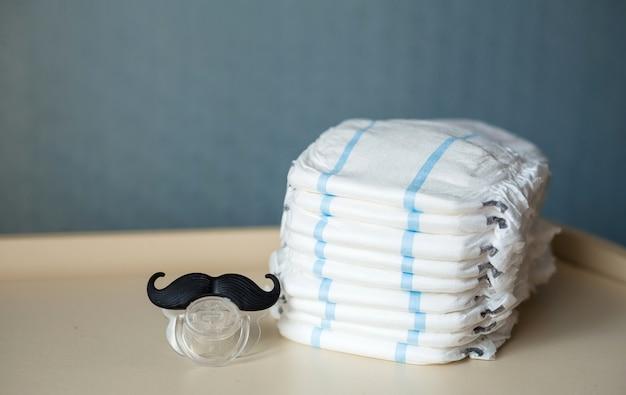 Een fopspeen in de vorm van een snor en een stapel babyluiers liggen op het dressoir. blauwe ruimte.