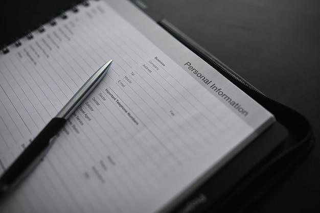 Een formulier invullen met persoonlijke gegevens. documenten in een map op de tafel om te vullen. handgeschreven informatie over de aanvrager.