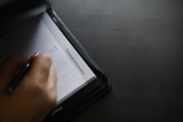Een formulier invullen met persoonlijke informatie documenten in een map op de tafel om in te vullen