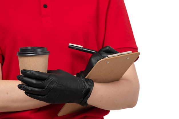 Een fornt weergave vrouwelijke koerier in rood shirt zwarte handschoenen met koffie en iets opschrijven