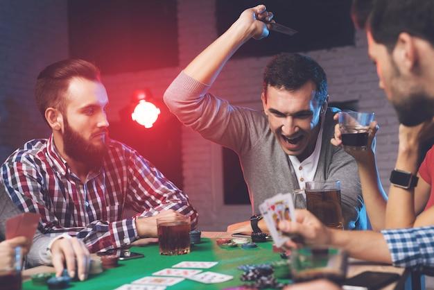 Een fortuinmens gooit kaarten op tafel.