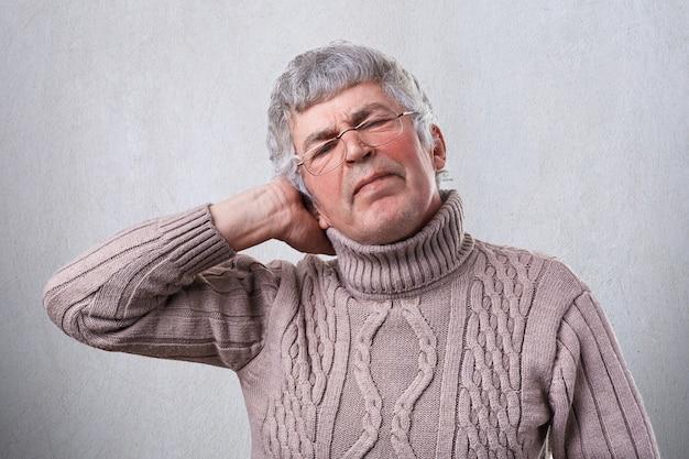 Een foto van de hogere mens die glazen draagt die van het harde werk worden vermoeid dat zijn hand op hoofd houdt. een volwassen man met hoofdpijn na het werken
