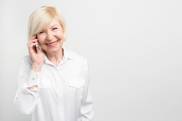 Een foto van de oude dame die een nieuwe telefoon gebruikt. ze test het graag. deze telefoon is haar favoriete telefoon.