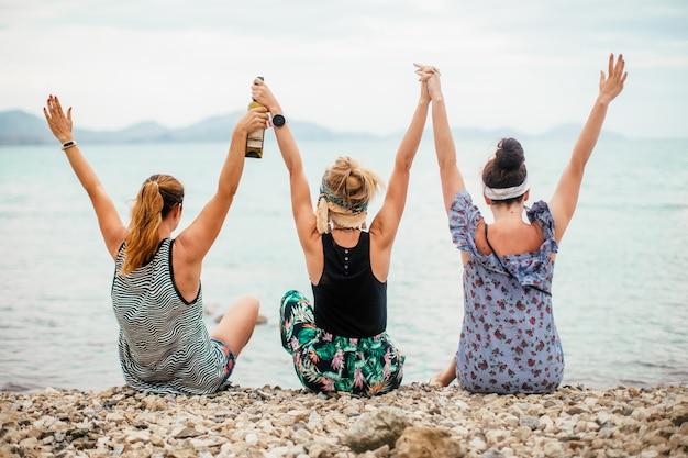 Een foto van drie jonge gelukkige vrouwen in de zomer aan de zeekust. het uitzicht vanaf de achterkant.