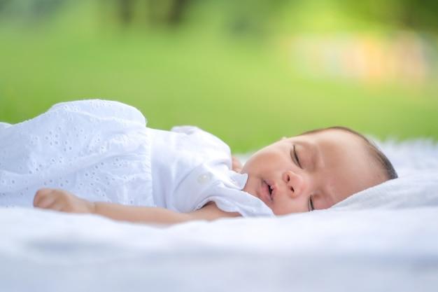 Een foto van een aziatische pasgeboren baby die vredig slaapt op een lange jas in een aziatische tuin.