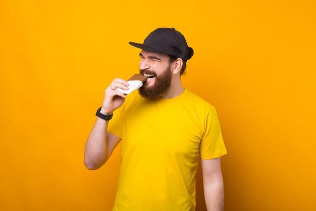 Een foto van een bebaarde man die chocolade eet en gelukkig is