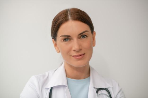 Een foto van een donkerharige vrouwelijke arts in een wit gewaad
