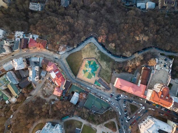 Een foto van een drone van boven de andreaskerk of de kathedraal van st. andreev, omringd door gebouwen en bomen in kiev, oekraïne foto van de drone
