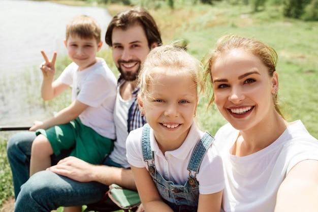 Een foto van een familie die samen aan de rand van de kust van riveer zit. ze kijken recht en glimlachen. jongen vertoont stuk symbool.