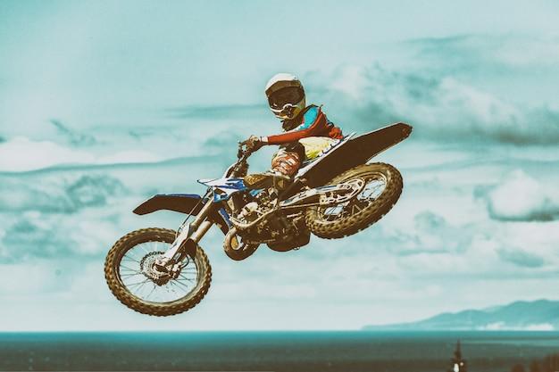 Een foto van een fietser die een stunt maakt en in de lucht springt